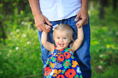 Girl learning to walk with dad royalty free stock image