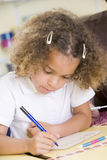 Girl learning to write numbers in primary class Royalty Free Stock Image
