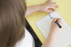 Girl learning to write numbers in primary class Stock Photos