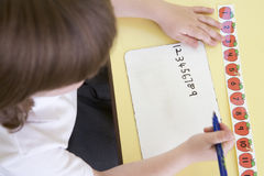 Girl learning to write numbers in primary class.  Royalty Free Stock Images