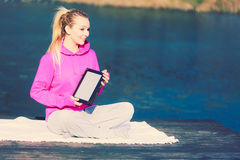 Girl learning yoga from tablet. Stock Images