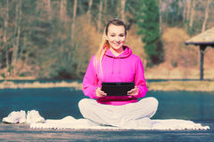 Girl learning yoga from tablet. Royalty Free Stock Photo