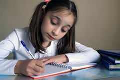 Girl learns lessons at home Royalty Free Stock Photos