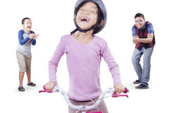 Girl learns riding a bike with dad and brother. Cute little girl try to ride a bicycle with her dad and brother, isolated on white background Royalty Free Stock Photos