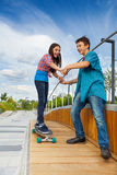 Girl learns riding skateboard holding boy's hands Stock Photo