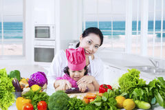 Girl learns to cook with her mother Stock Image
