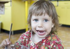 The girl learns to eat. The little girl learns to eat royalty free stock image