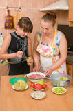 The girl learns to make a dinner. Stock Photography