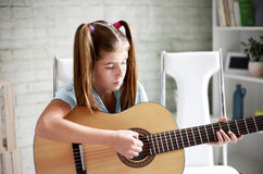 Girl learns to play guitar Stock Photo