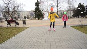Girl learns to roller skate on paved road in Park. family vacation in the Park stock video