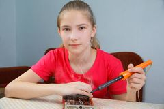 The girl learns to solder at home. The teenager is learning to solder. Repair of a computer graphics card stock images