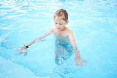 Girl learns to swim. Little girl learns to swim in the pool with blue water Stock Images