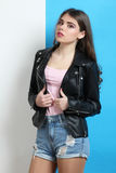 Girl in leather jacke. Stylish girl in leather jacket posing on white and blue background royalty free stock photos