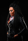 Girl in a leather jacket. Black background. Creative hairstyle, dreadlocks. Girl with an unusual hairdo. Black long hair. dreadlocks Royalty Free Stock Photo