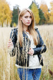 The girl in a leather jacket among a  grass Royalty Free Stock Photo