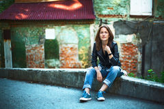 A girl in a leather jacket, jeans and sneakers; Sitting near a r. Oad against the wall of an old house Royalty Free Stock Images