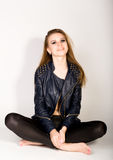 Girl in a leather jacket leather shorts is based on a stepladder Royalty Free Stock Image