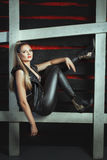 Girl in a leather jacket and pants posing studio. Royalty Free Stock Photography