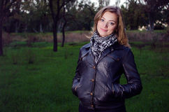 Girl in leather jacket. In the park stock images