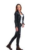 Girl in leather jacket pose walking in studio background while l stock image