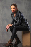 Girl in leather jacket posing in studio seated resting Stock Photography