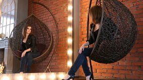 Girl in a leather jacket preening before the mirror in a designer chair.  stock footage