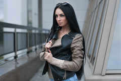 Girl in a leather jacket standing near the building. Brunette Royalty Free Stock Image