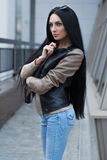 Girl in a leather jacket standing near the building. Europe Stock Images