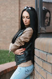 Girl in a leather jacket standing near the building Royalty Free Stock Photography