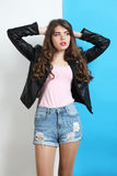Girl in leather jacket. Stylish girl in leather jacket posing on white and blue background Royalty Free Stock Photography