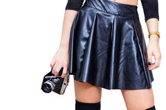 Girl with leather skirt and vintage camera. Woman from waist to knees in black leather skirt holding retro photo camera in hand Royalty Free Stock Photography
