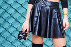Girl with leather skirt and vintage camera. Woman from waist to knees in black leather skirt holding retro photo camera in hand Stock Photo