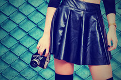 Girl with leather skirt and vintage camera. Woman from waist to knees in black leather skirt holding retro photo camera in hand Royalty Free Stock Photo