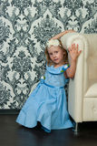 Girl and leather sofa Stock Photography