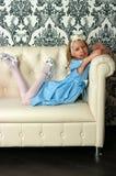 Girl and leather sofa Stock Photos
