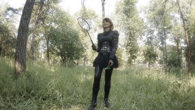 Girl in leather suit plays badminton on the grass stock footage