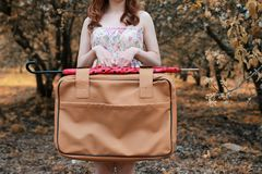 Girl with leather suitcase for travel in the autumn park on walk Royalty Free Stock Photos