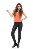 Girl In Leather Trousers Giving Thumb Up. Smiling young woman in black leather trousers, orange shirt and boots standing with hands on hip, looking at camera and Royalty Free Stock Photos