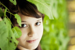 Girl between leaves Stock Photos