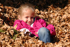 Girl in Leaves. A young girl sits quietly in a pile of leaves enjoying the warmth of the sun on a late autumn day Royalty Free Stock Photography