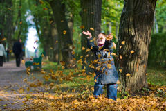 Girl and leaves at autumn. Little happy girl with two funny ponytails throws and try to catch yellow leaves royalty free stock photography