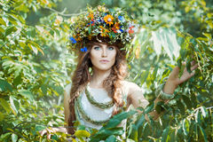 Girl among leaves trees with a wreath on his head. royalty free stock image