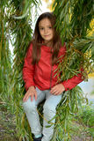 Girl in the leaves of a weeping willow. Portrait of a cute teeanager girl sitting on a swing  made of the branches of the weeping willow Stock Photo