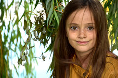Girl in the leaves of a weeping willow. Portrait of a cute teenager girl in the leaves of a weeping willow Royalty Free Stock Images