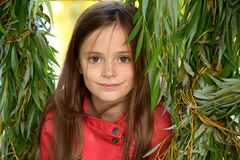 Girl in the leaves of a weeping willow. Portrait of a cute teenager girl in the leaves of a weeping willow royalty free stock photography