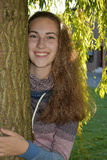 Girl in the leaves of a weeping willow. Portrait of a cute teenager girl in the branches of the weeping willow Royalty Free Stock Image