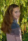 Girl in the leaves of a weeping willow. Portrait of a cute teenager girl  in the branches of the weeping willow Stock Image