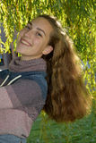 Girl in the leaves of a weeping willow. Portrait of a cute teenager girl  in the branches of the weeping willow Stock Images