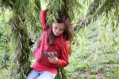 Girl in the leaves of a weeping willow. Portrait of a cute teenager girl sitting on a swing  made of the branches of the weeping willow, looking on her cellphone Royalty Free Stock Images