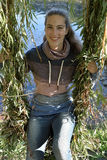 Girl in the leaves of a weeping willow Royalty Free Stock Photo